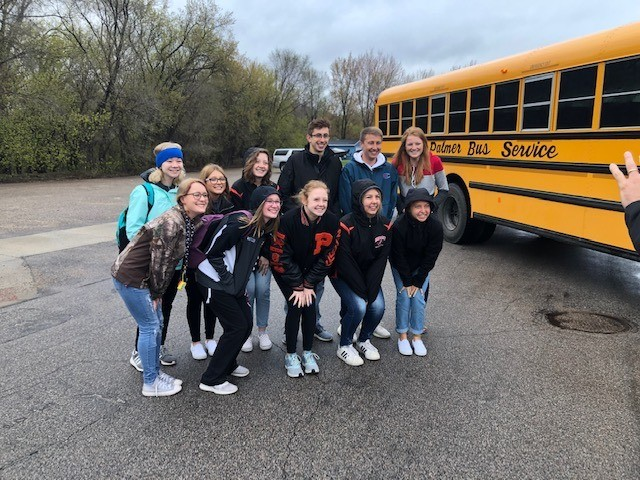 Group of students in front of a bus