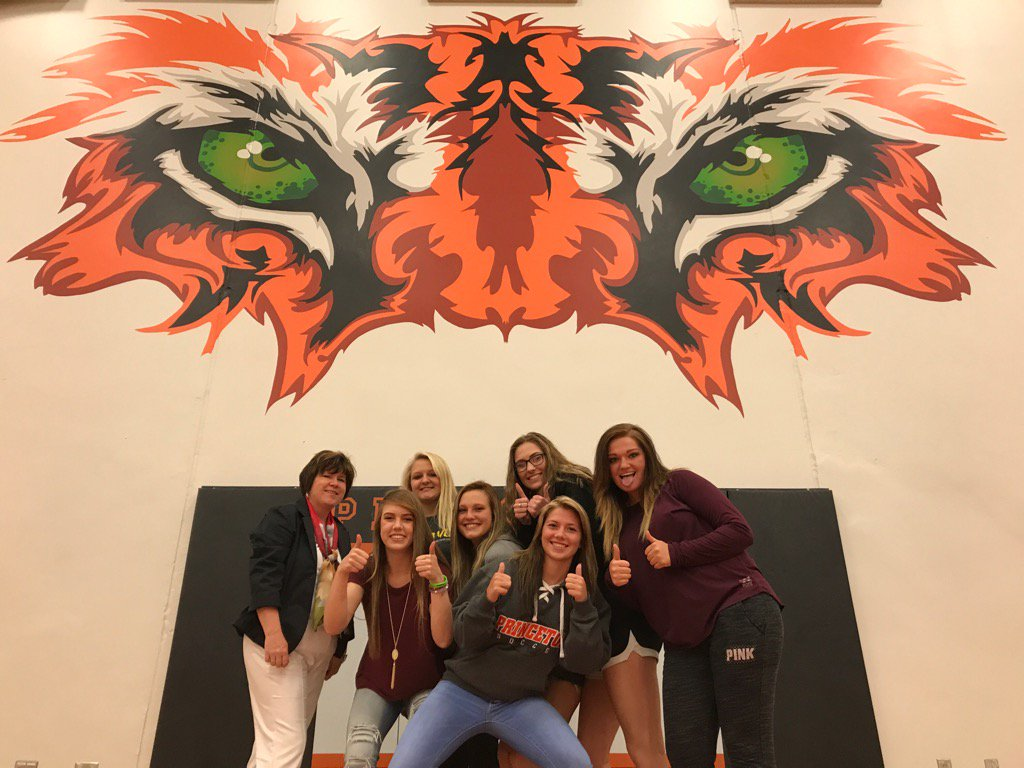 HS principal with students standing by painting of tiger
