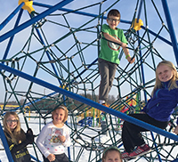 students playing on the spider gym outside