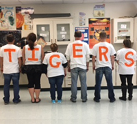 teacher with letters on the back of their white shirts spelling TIGER to show pride