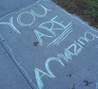you are amazing written in chalk by the students on the sidewalk outside the middle school