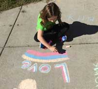 young female student writing love in chalk on the sidewalk